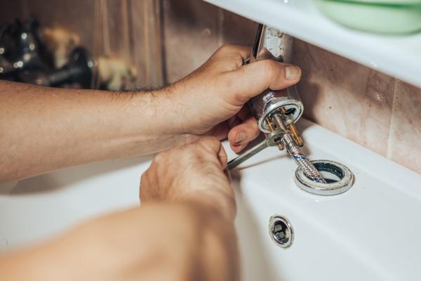 A plumber replacing a sink fixture.